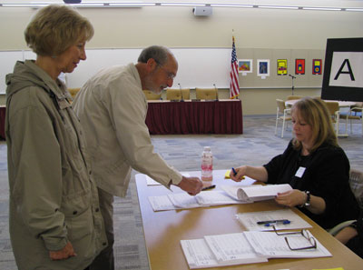 Robert and Susan Alessi of Wheatfield sign in to vote at the N-W Adult Learning Center. (photo by Susan Mikula Campbell)