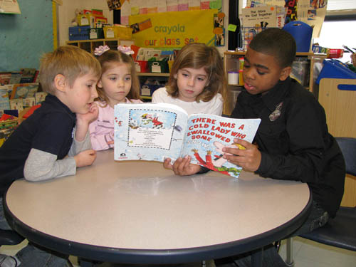 Errick Road fourth-grader Davon Ware helps out kindergarten teachers Lori Bellacose and Erica Tortorella by reading stories to their students.