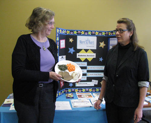Debra Hoffman, registered dietician and certified diabetes educator at Mount St. Mary's Hospital and Health Center, shows the `healthy plate` she uses in diabetes classes to Eileen Arway, home medical equipment, respiratory and diabetic shoe consultant at Health System Services in Wheatfield. A diabetes awareness program was held at the Wheatfield business on Nov. 19.