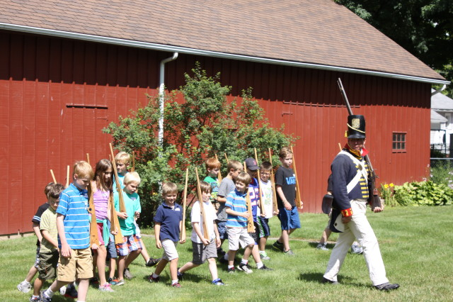 Children march behind a War of 1812 soldier from Old Fort Niagara during one of the History Center's summer children's programs.