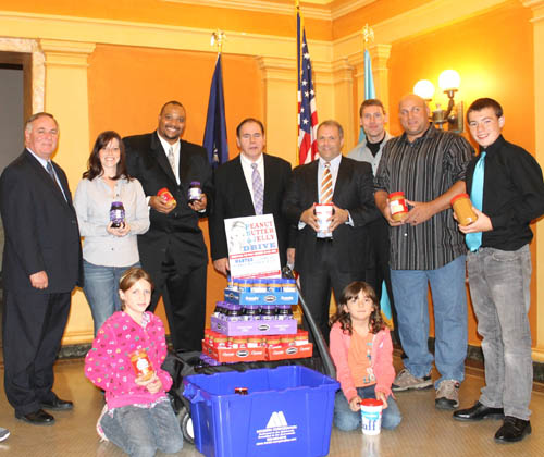 Lockport's Legislature delegation is all smiles after giving the local `Peanut Butter & Jelly Drive` a big boost Tuesday night. Three Niagara County lawmakers representing Lockport donated six-dozen jars of peanut butter and jelly to the second annual food drive. Pictured from left are Niagara County Legislator Tony Nemi, Tina Sheeley, New York State Courts Sgt. Pete Robinson, Legislator Wm. Keith McNall, Majority Leader Rick Updegrove, Mike Barlass and Gary Chapman. Chapman's children are in the foreground, guarding the wagonload of sandwich spreads donated by McNall, Updegrove and Nemi.