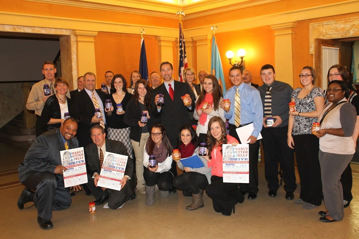 Members of the Niagara County Legislature's Republican-led Majority Caucus and their legislative interns are surrounded by volunteers for the third annual Peanut Butter and Jelly Drive at the Niagara County Courthouse after the Majority lawmakers donated 12 dozen jars of peanut butter, jelly and marshmallow fluff to the local charity, which last year netted more than 9,000 jars of the sandwich spreads for area food pantries. The Majority's donation is becoming a sort of annual ritual in Lockport, with the GOP caucus using the opportunity to give back to their community. The legislatures' donation was funded entirely by donations from the lawmakers, and no public funds were used.