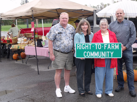 Members of Wheatfield's Agriculture Focus Group - Donald Proefrock, Kristine Taylor, Karen Frieder and David Anastasi - are shown at the town's Farmers Market last week with one of the new `right to farm` signs. (photo by Bill Frieder)