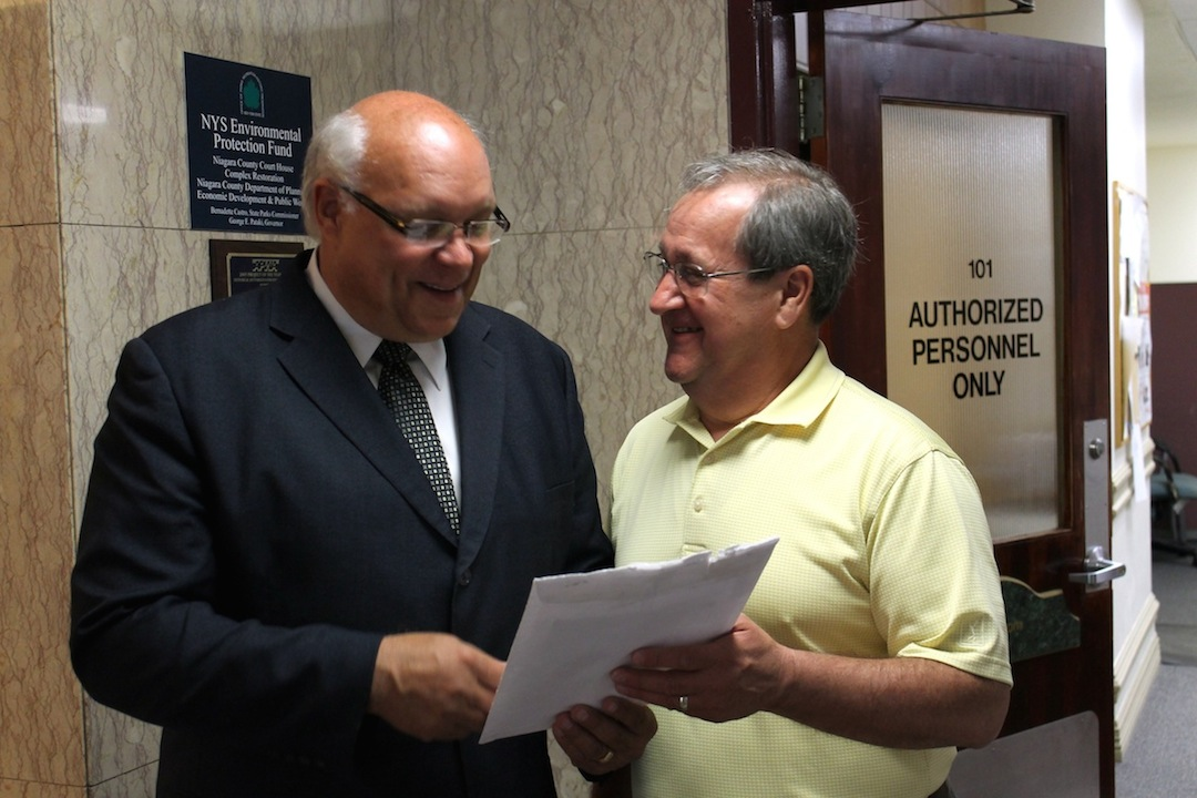 Newly appointed 4th District Coroner Michael A. Ross, left, is congratulated by 3rd District Coroner Ken Lederhouse Tuesday in Lockport. Lederhouse, the county's longest-serving coroner, was on-hand to watch as county lawmakers appointed Ross to fill a post left vacant by the unexpected resignation last month of former coroner Richard Rutland of Newfane. Lederhouse and 2nd District Coroner Joe Mantione had been actively managing coroner calls in Niagara County's vast 4th Coroner District, which covers the entire Lake Ontario shore and much of the county's north, since Rutland's resignation became effective at the end of April.