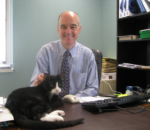 New SPCA of Niagara Executive Director Andrew Bell is welcomed by Sam the cat. (photo by Susan Mikula Campbell)