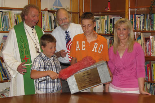 Max Kijowski (front left) dusts off the time capsule box, held by Michael Manth of Wheatfield, as Pastor Karl Haeussler, former Principal Paul Gerlach, and school alumnus Carolyn Taylor look on. The box will be opened July 17.