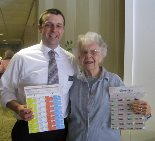 Christopher Sauls of Summit Park Pharmacy and one of his regular customers, Jessie Albright of Crestwood Commons, display the front and back of the new medication sheets for easier medication management. (photo by Susan Mikula Campbell)