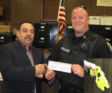 Charles Teixeira, Town of Niagara councilman and police commissioner, accepts a check from Officer Craig Guiliani, president of the Town of Niagara Police Club, to pay for an additional Taser unit for the town's police department.