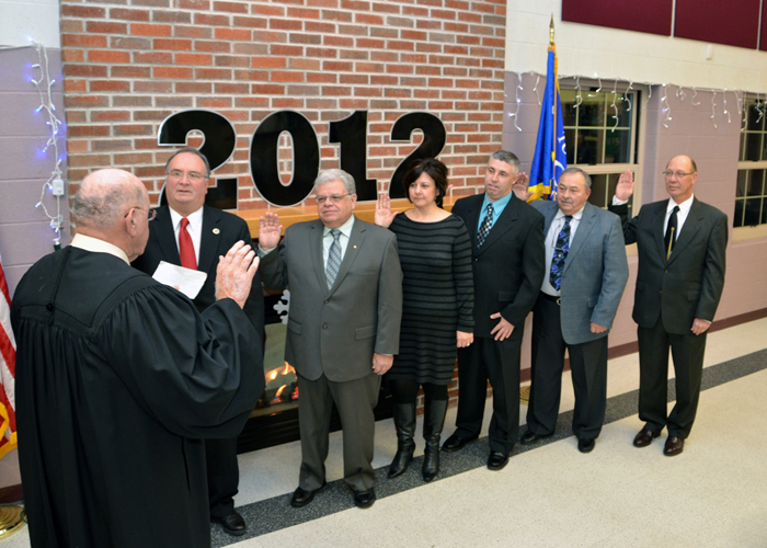 Town Justice John Teixeira, left, did the honors swearing in Highway Superintendent Robert Herman, Supervisor Steve Richards, Town Clerk Sylvia Virtuoso, Councilman Robert Clark, Town Justice James Faso and Councilman Danny Sklarski. (photo by Marc Carpenter)