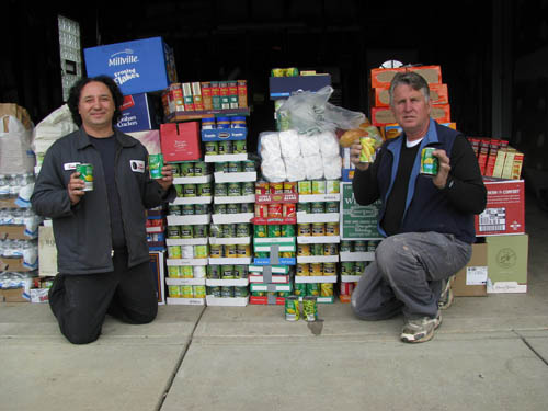 Gene Colucci of Gene's Wholesale Tires, president of the Town of Niagara Business and Professional Association, and Gary Strenkoski of Strenkoski Brothers, chairman of the Electric Lights Parade show off the food collected for Community Missions at this year's parade. (photo by Susan Mikula Campbell)