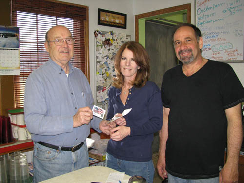 Roger Andrews uses his Thank A Vet card at Salisa's in Wheatfield. At right are diner owners Lisa and Sal Buscaglia. (photo by Susan Mikula Campbell)