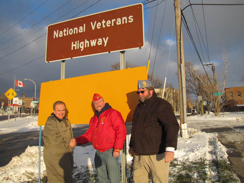 State Sen. George Maziarz shakes the hand of Commandant Doug Woolley of the Marine Corps League, Lt. Bobo Detachment, at the sign marking the National Veterans Highway (Route 62) in Niagara Falls. Joining them is Bob Reed of the Sons of the American Legion Post 880 in Eden, who led the call for the designation.