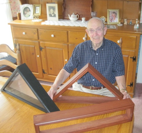 Wayne Cooper, a World War II veteran, poses behind his hand-made U.S. flag cases.