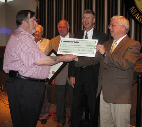 Dennis A. Peterson hands Town Board members an enlarged check for $32,987.44 representing the amount the town received as a settlement from Time Warner Cable. The board presented Peterson with a proclamation naming him the 2011 Citizen of the Year for bringing the misdirection of cable franchise fees to its attention.