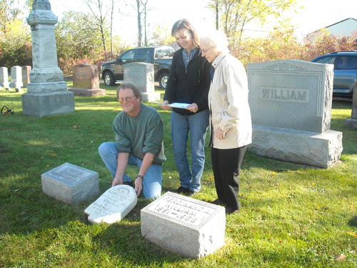 Williams family descendants place the gravestone of August Williams in the family plot at St. James Cemetery.  From left are Bruce Genewich, great nephew from Lockport; Ann Clingersmith, a great-great niece from Niagara Falls and Imogene Genewich, a niece from Lockport.