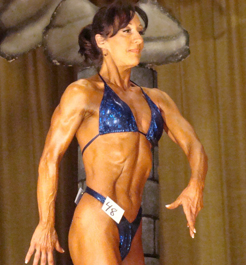 Sue Manera poses for the judges in bodybuilding competition.