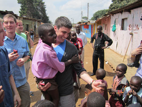 N-W grad Michael Pittman is shown with some of the children he met in Kenya with fellow members of the University of Rochester's YellowJackets.